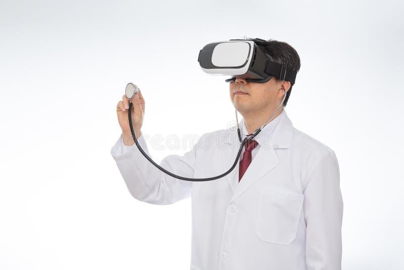 Doctor de sexo masculino que lleva los vidrios de la realidad virtual aislados en el fondo blanco fotos de archivo