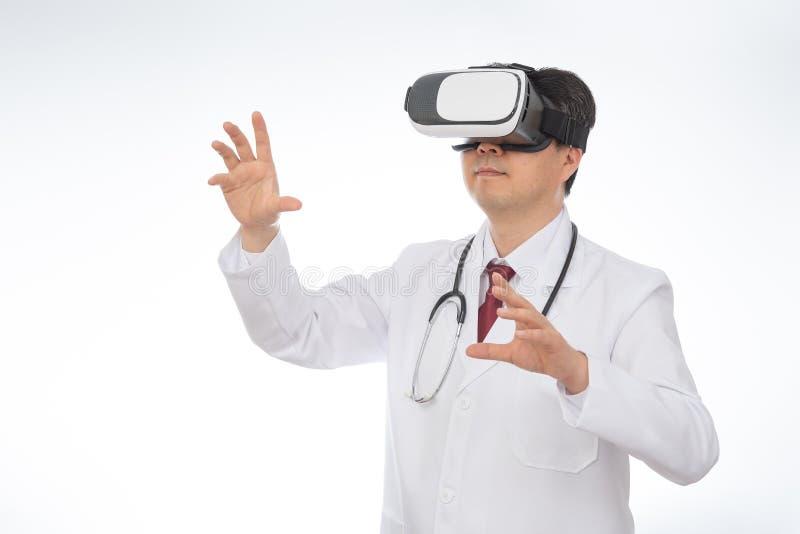 Doctor de sexo masculino que lleva los vidrios de la realidad virtual aislados en el fondo blanco fotografía de archivo