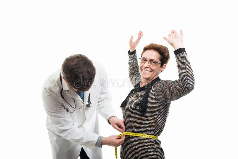 Doctor de sexo masculino que mide al paciente mayor femenino feliz imagen de archivo libre de regalías