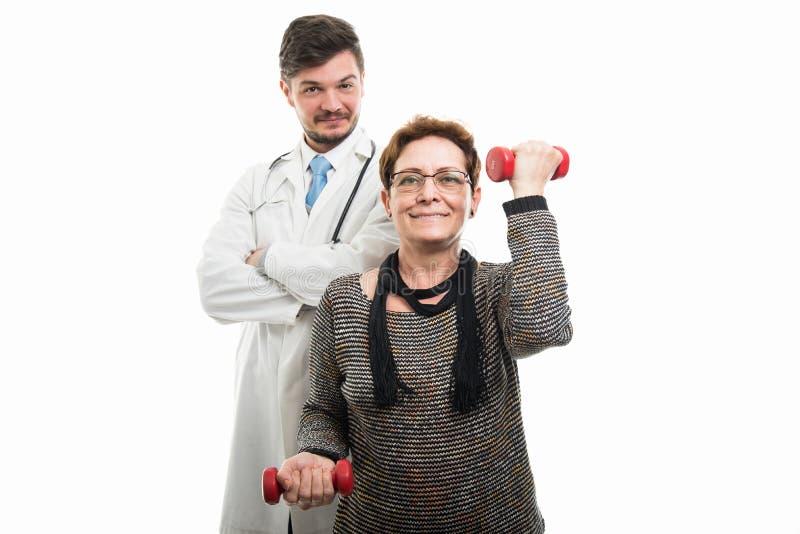 Doctor de sexo masculino que mira al paciente femenino que trabaja con pesa de gimnasia fotos de archivo