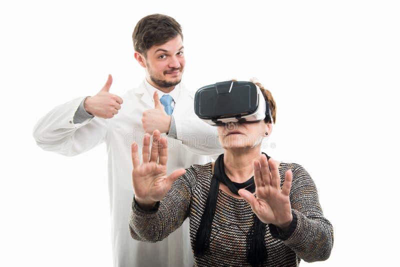 Doctor de sexo masculino que muestra como y gafas del vr del paciente que llevan femenino foto de archivo