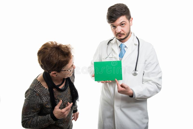 Doctor de sexo masculino que señala en tablero verde al paciente mayor femenino foto de archivo libre de regalías