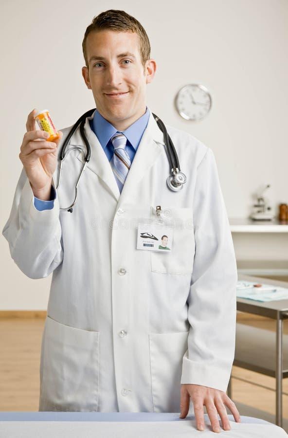 Doctor de sexo masculino que sostiene hacia fuera la botella de la medicación imagen de archivo