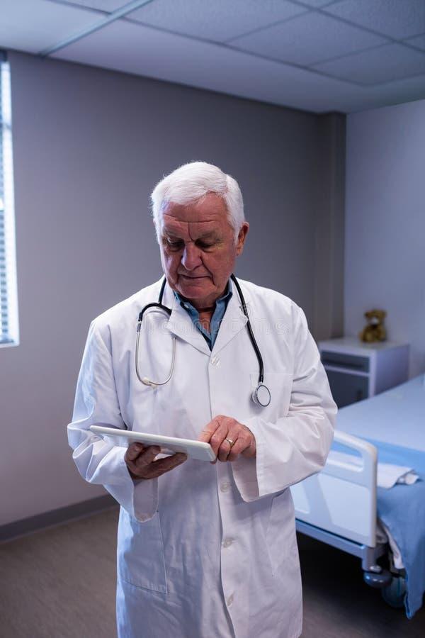 Doctor de sexo masculino que usa la tableta digital en sala fotografía de archivo