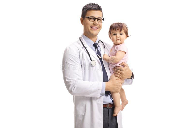 Doctor de sexo masculino sonriente del pediatra que detiene a un bebé imágenes de archivo libres de regalías