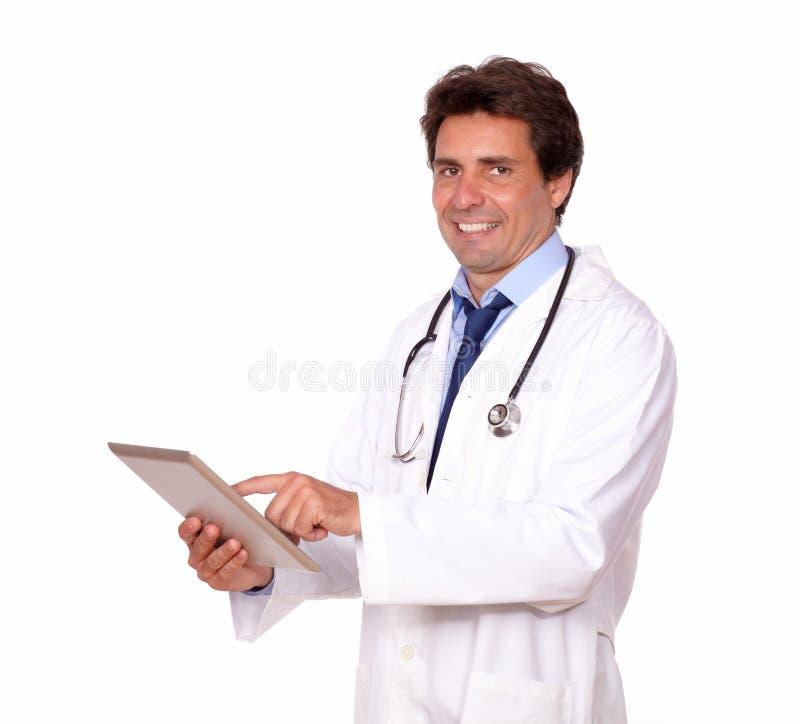 Doctor de sexo masculino sonriente que trabaja en la PC de la tableta fotos de archivo libres de regalías