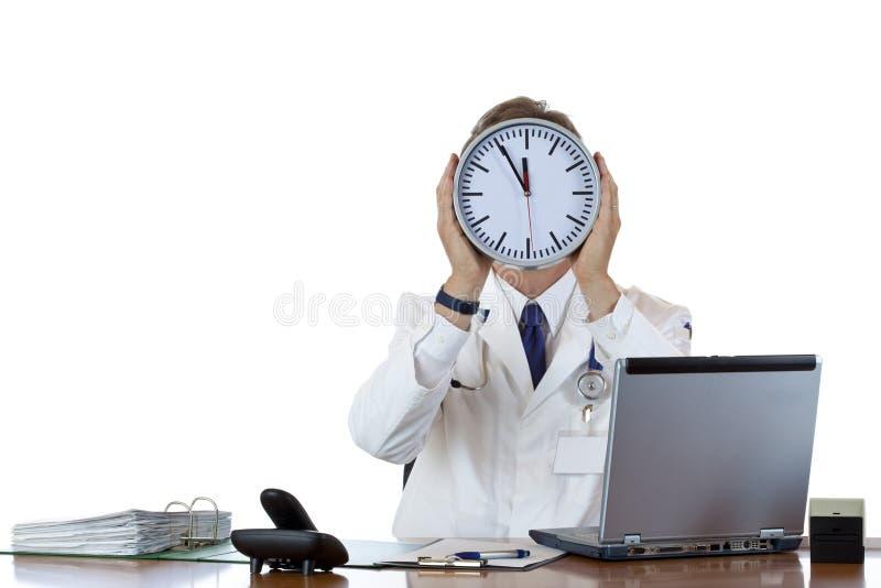 Doctor de sexo masculino tensionado en oficina bajo presión de tiempo imagenes de archivo
