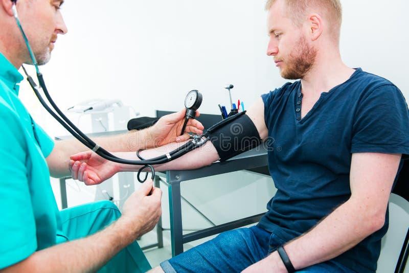 Doctor de sexo masculino usando el sphygmomanometer con el estetoscopio que comprueba la presión arterial a un paciente masculino fotografía de archivo