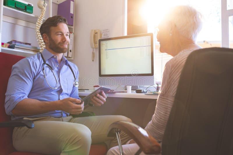 Doctor de sexo masculino usando la tableta digital mientras que habla con la mujer mayor en cl?nica fotografía de archivo