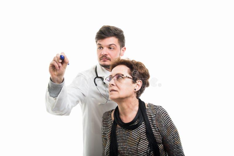 Doctor de sexo masculino y dibujo paciente mayor femenino con el marcador azul imagen de archivo libre de regalías