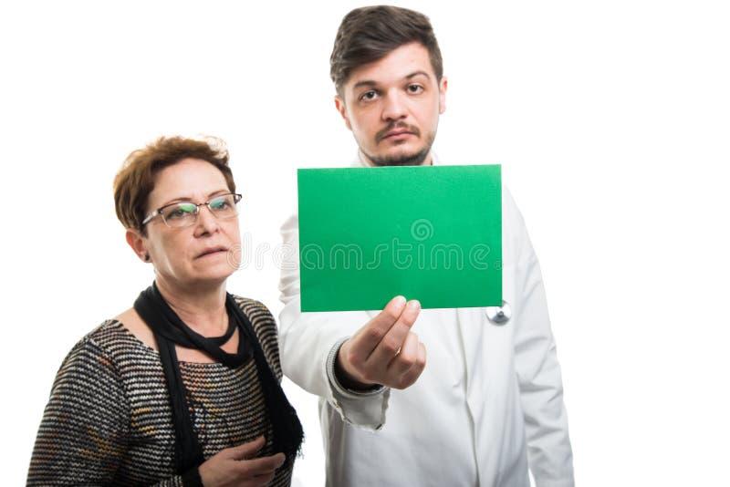 Doctor de sexo masculino y paciente femenino que mira para poner verde al tablero fotos de archivo libres de regalías