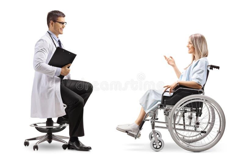 Doctor de sexo masculino y un paciente femenino en una silla de ruedas que tiene una conversación imágenes de archivo libres de regalías