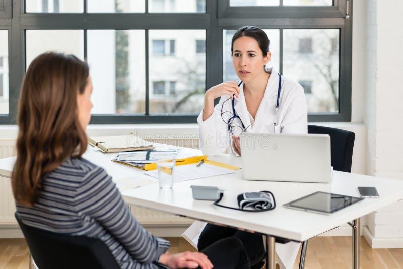 Doctor dedicado que escucha su paciente durante una consulta privada imagen de archivo libre de regalías