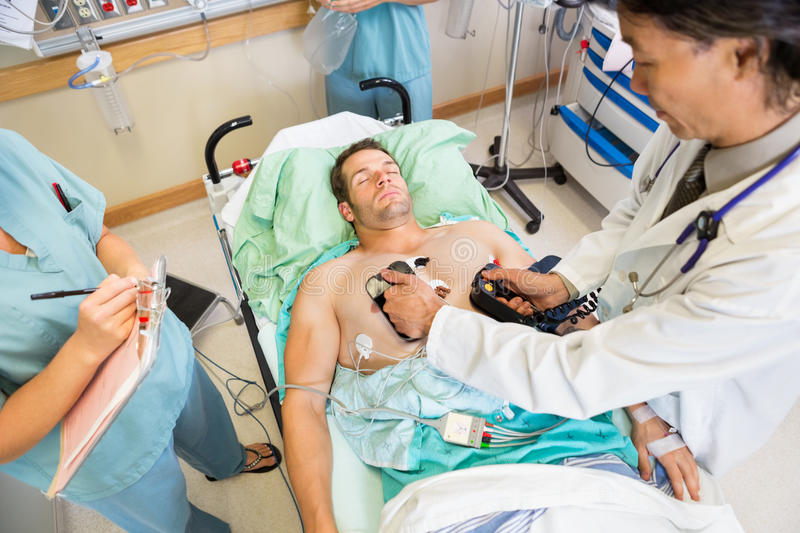 Doctor Defibrillating Male Patient In Hospital stock photos