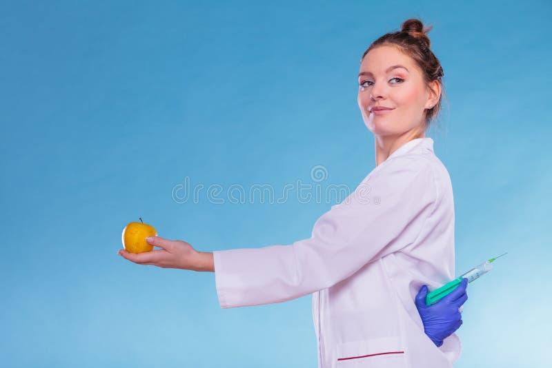 Doctor del científico con la manzana y la jeringuilla Comida del GM fotos de archivo libres de regalías