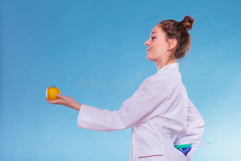 Doctor del científico con la manzana y la jeringuilla Comida del GM imagen de archivo
