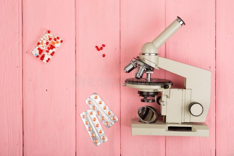 Doctor del científico del lugar de trabajo - microscopio, píldoras en la tabla de madera rosada foto de archivo libre de regalías
