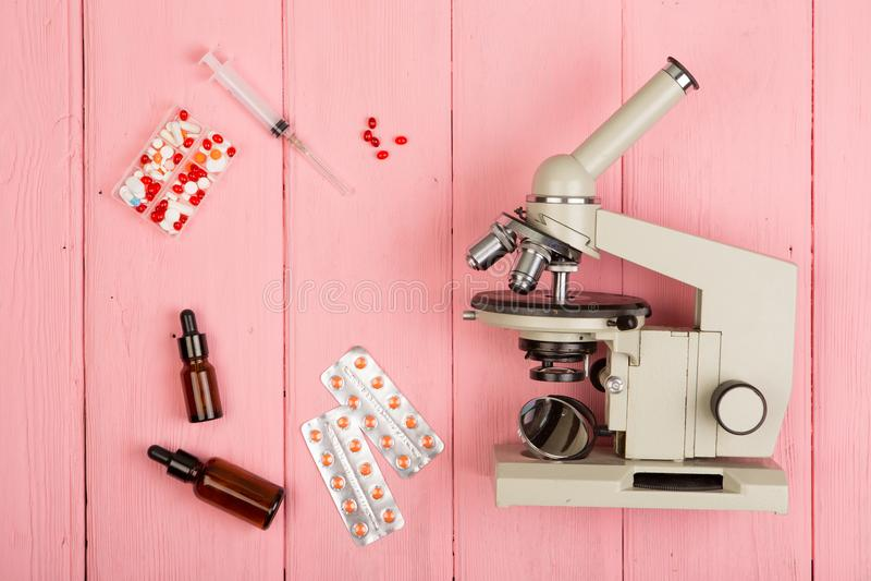 Doctor del científico del lugar de trabajo - microscopio, píldoras, jeringuilla en la tabla de madera rosada fotos de archivo libres de regalías