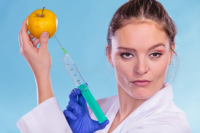 Doctor del científico que inyecta la manzana Comida del GM foto de archivo