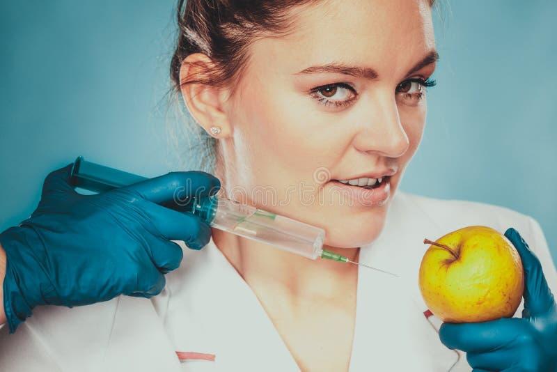 Doctor del científico que inyecta la manzana Comida del GM imágenes de archivo libres de regalías