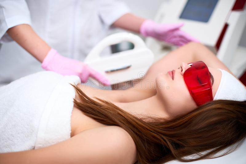 Doctor del cosmetólogo que hace la depilación del retiro del pelo de los elos en los axilas bonitos de la mujer joven en salón be foto de archivo libre de regalías