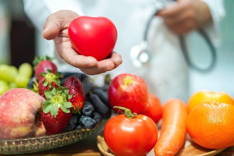 Doctor del nutricionista que sostiene la naranja con las diversas frutas y verduras fotos de archivo libres de regalías
