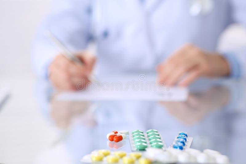 Doctor desconocido de la mujer en el trabajo en el hospital Píldoras en la tabla de cristal Médico de sexo femenino joven describ fotos de archivo