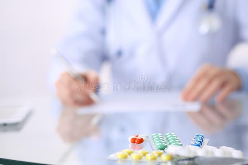 Doctor desconocido de la mujer en el trabajo en el hospital Píldoras en la tabla de cristal Médico de sexo femenino joven describ fotos de archivo libres de regalías