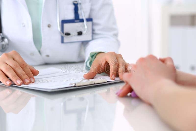 Doctor desconocido y paciente que hablan mientras que se sienta en el escritorio en la oficina del hospital, primer de manos huma imagen de archivo libre de regalías