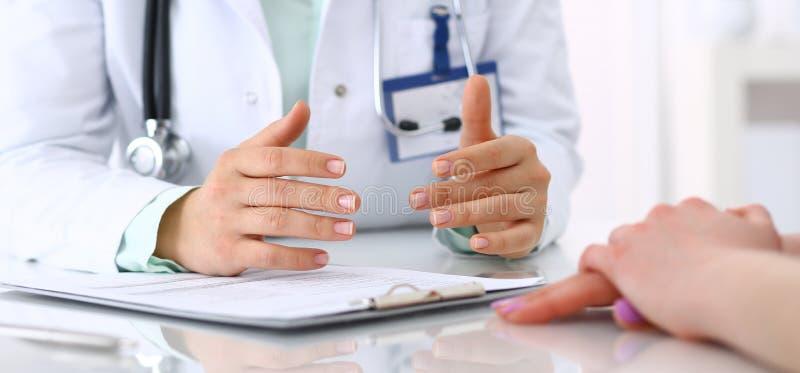 Doctor desconocido y paciente que hablan mientras que se sienta en el escritorio en la oficina del hospital, primer de manos huma fotos de archivo libres de regalías