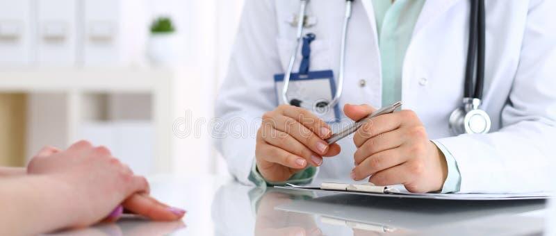 Doctor desconocido y paciente que hablan mientras que se sienta en el escritorio en la oficina del hospital, primer de manos huma fotos de archivo
