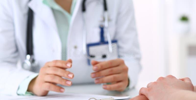 Doctor desconocido y paciente que hablan mientras que se sienta en el escritorio en la oficina del hospital, primer de manos huma foto de archivo libre de regalías