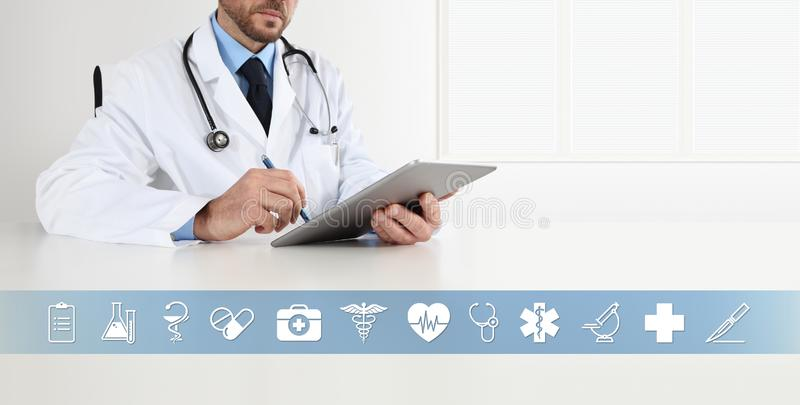 Doctor at desk office write on digital tablet, with symbols and medical icons, web banner and copy space royalty free stock image