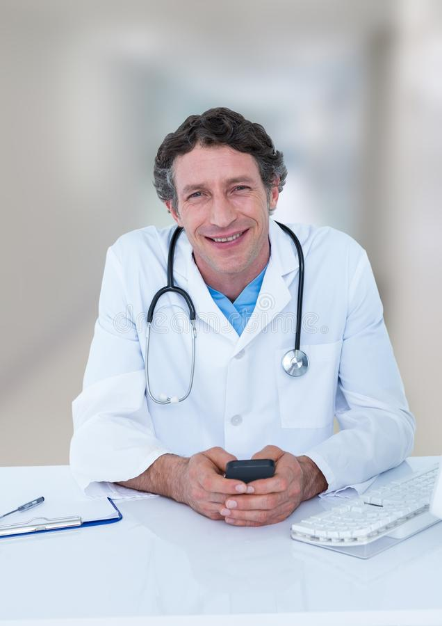 Doctor at desk with phone against blurred hallway. Digital composite of Doctor at desk with phone against blurred hallway royalty free stock photography