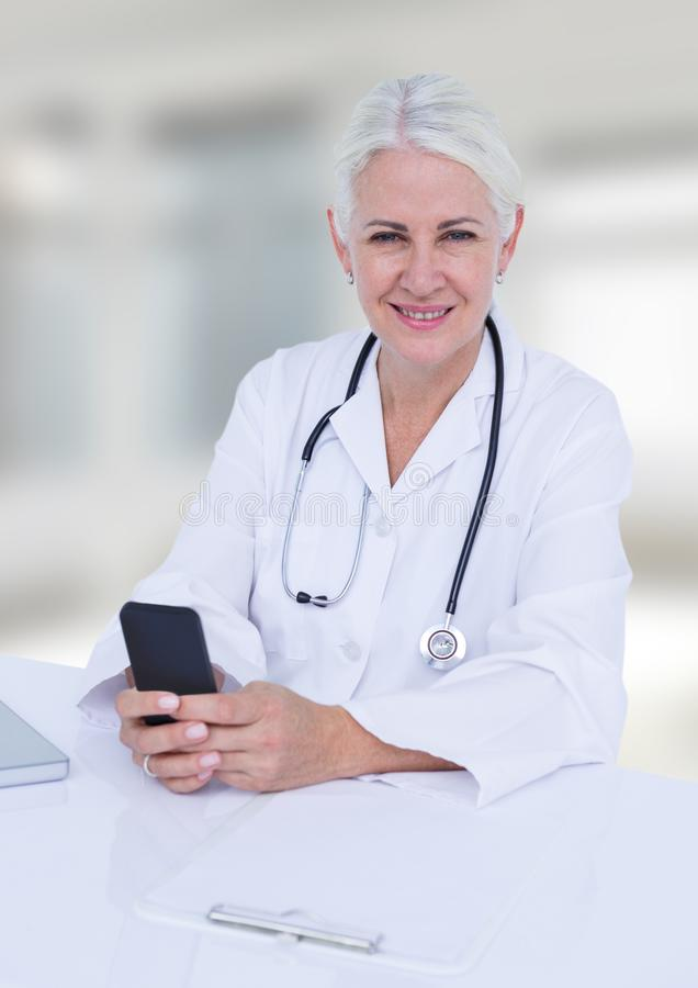 Doctor at desk with phone against white blurred windows. Digital composite of Doctor at desk with phone against white blurred windows stock photography