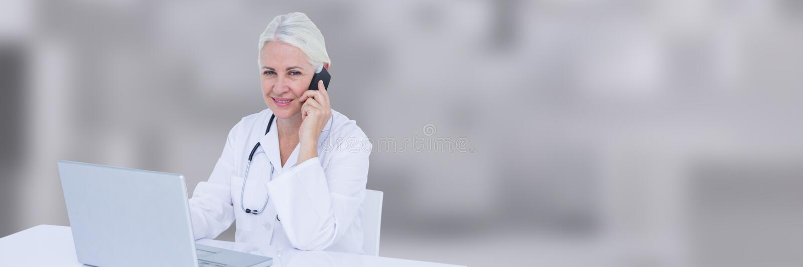 Doctor at desk talking on phone against blurry grey background. Digital composite of Doctor at desk talking on phone against blurry grey background stock photo