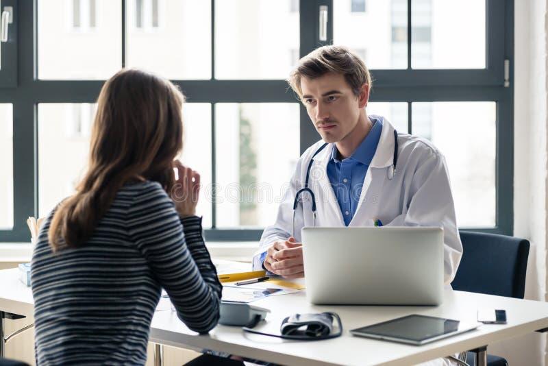 Doctor devoto joven que escucha con la atención a su paciente fotos de archivo libres de regalías
