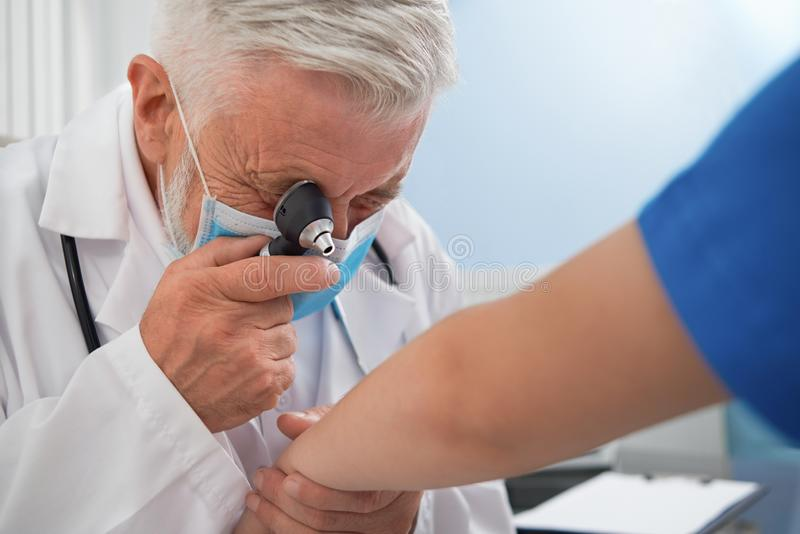 Doctor diagnosing disease of skin on patient`s hand. royalty free stock photos