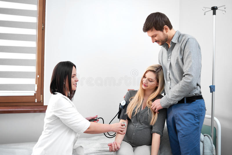 Doctor diagnosing for pregnant woman of measuring blood pressure. stock images