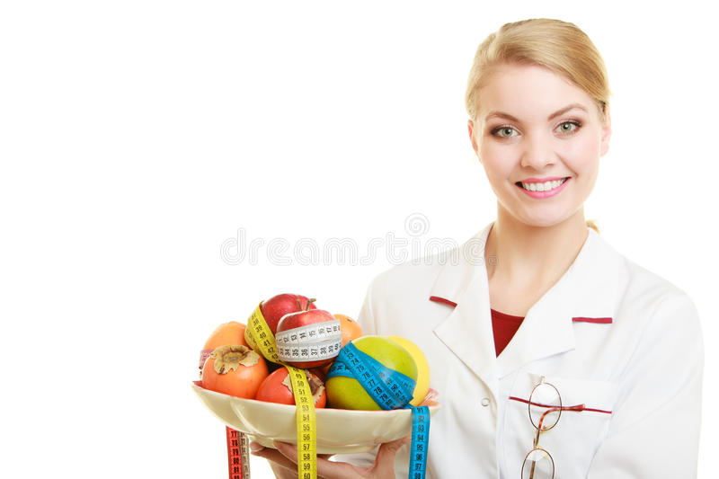 Doctor dietitian recommending healthy food. Diet. Woman in lab coat holding fruits and measure tapes isolated. Doctor dietitian with healthy food. Diet royalty free stock photos
