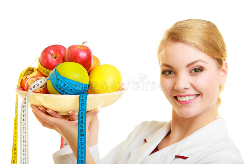 Doctor dietitian recommending healthy food. Diet. Woman in white lab coat holding fruits and colorful measure tapes isolated. Doctor dietitian recommending royalty free stock photos