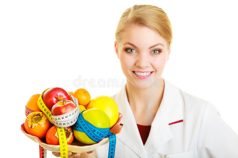 Doctor dietitian recommending healthy food. Diet. Woman in white lab coat holding fruits and colorful measure tapes isolated. Doctor dietitian recommending stock photography