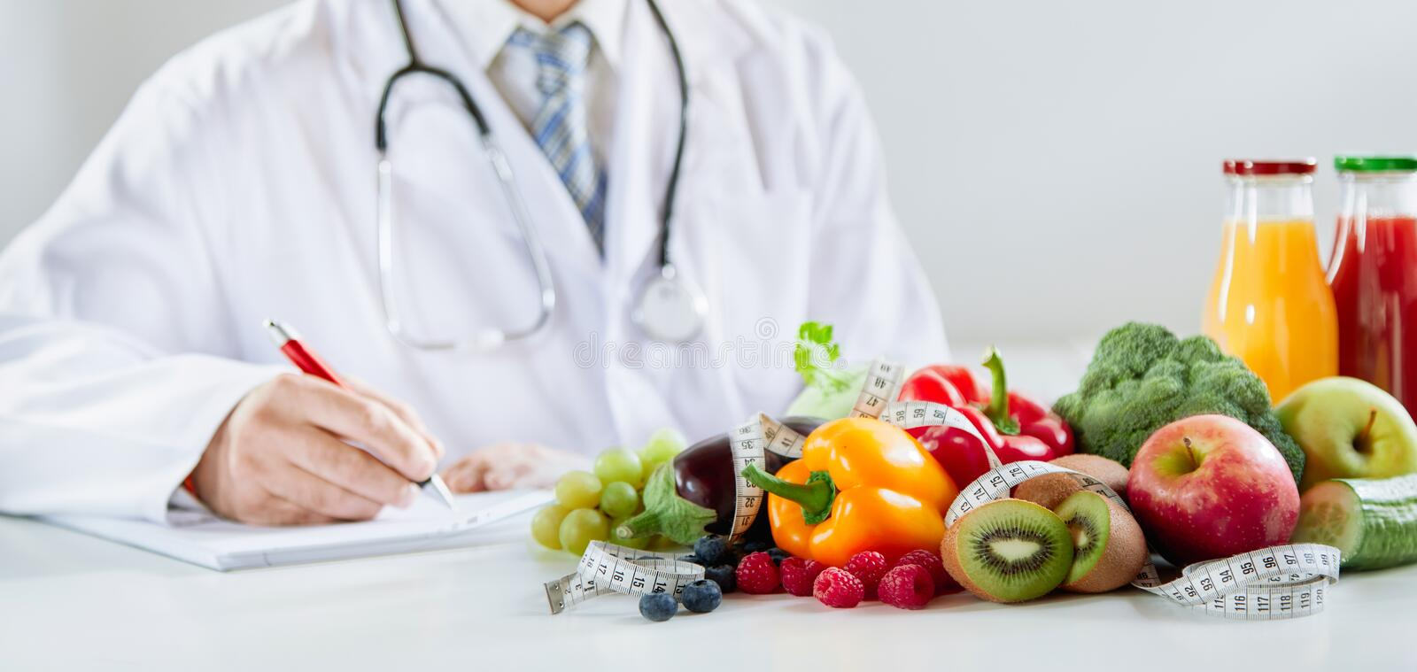 Doctor or dietitian writing a healthy food recipe. With assorted fresh fruit and vegetables in the foreground with smoothies stock images