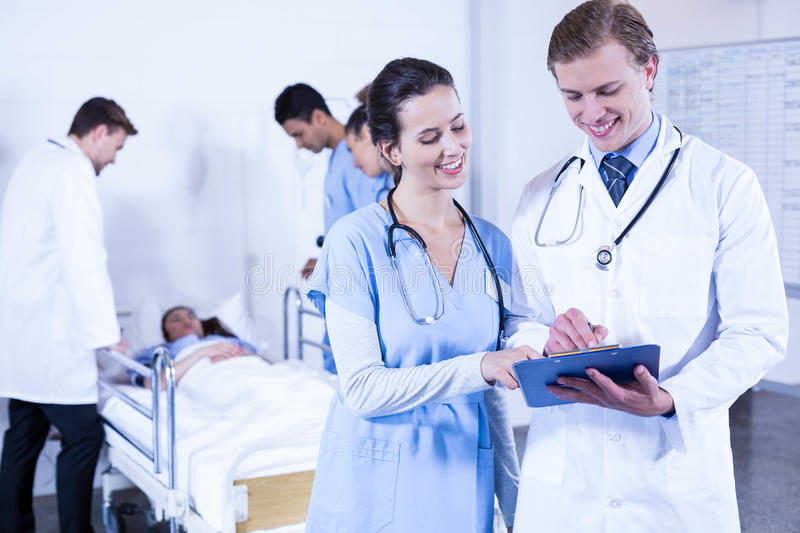 Doctor discussing paperwork on clipboard stock photo