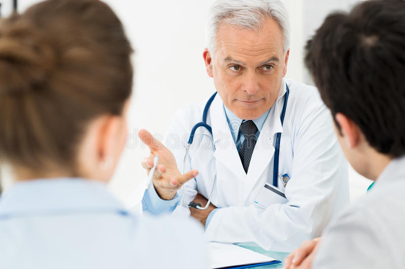 Doctor discussing with patients stock photo