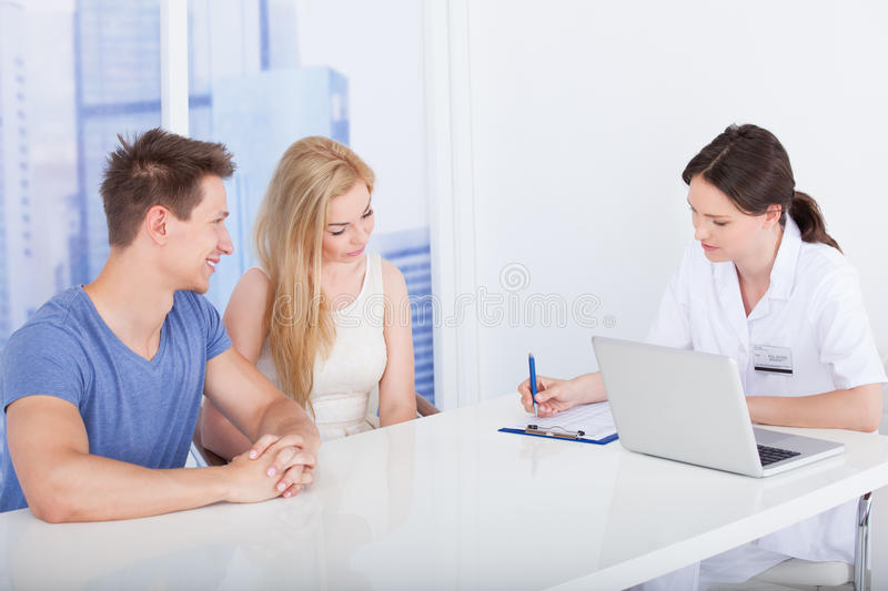 Doctor discussing report with young couple in clinic. Female doctor discussing report with young couple at desk in clinic royalty free stock images