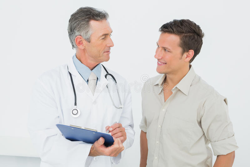 Doctor discussing reports with patient in office stock photos
