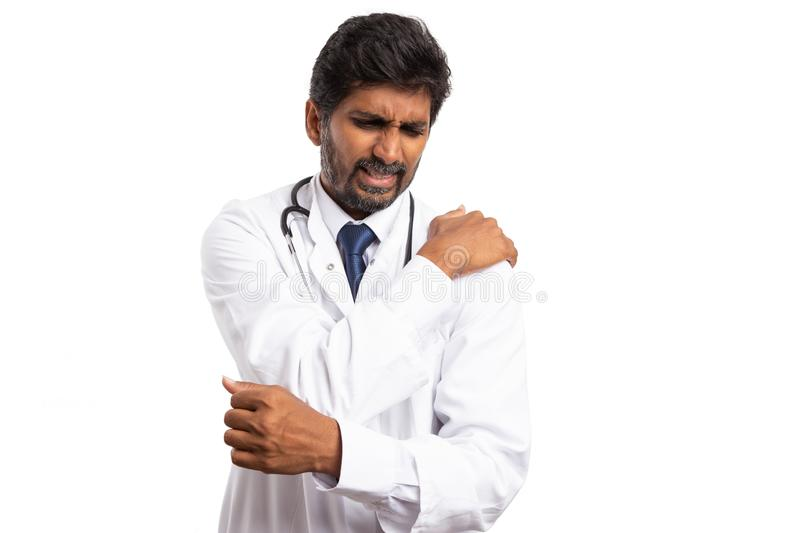 Doctor dislocated shoulder. Indian desperate doctor touching dislocated shoulder with painful expression isolated on white background stock photos