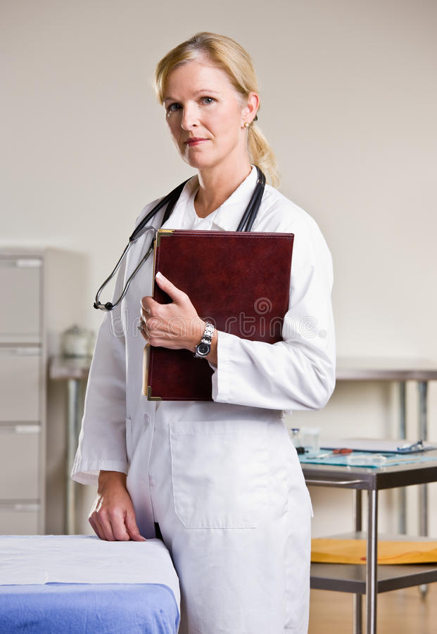 Doctor in doctor office holding notebook stock image