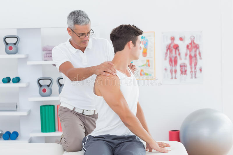 Doctor doing back adjustment. In medical office stock image